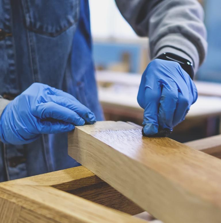 Osoba dokonująca renowacji drewna